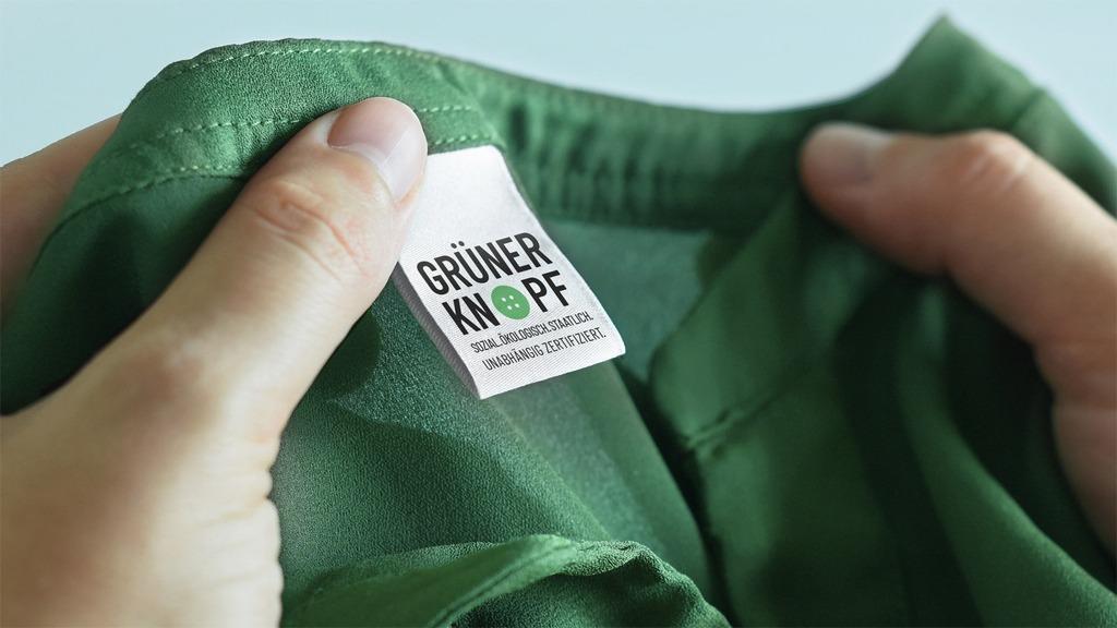 Der grüne Knopf ist ein staatliches Textilsiegel, das nachhaltige Kleidung kennzeichnet.