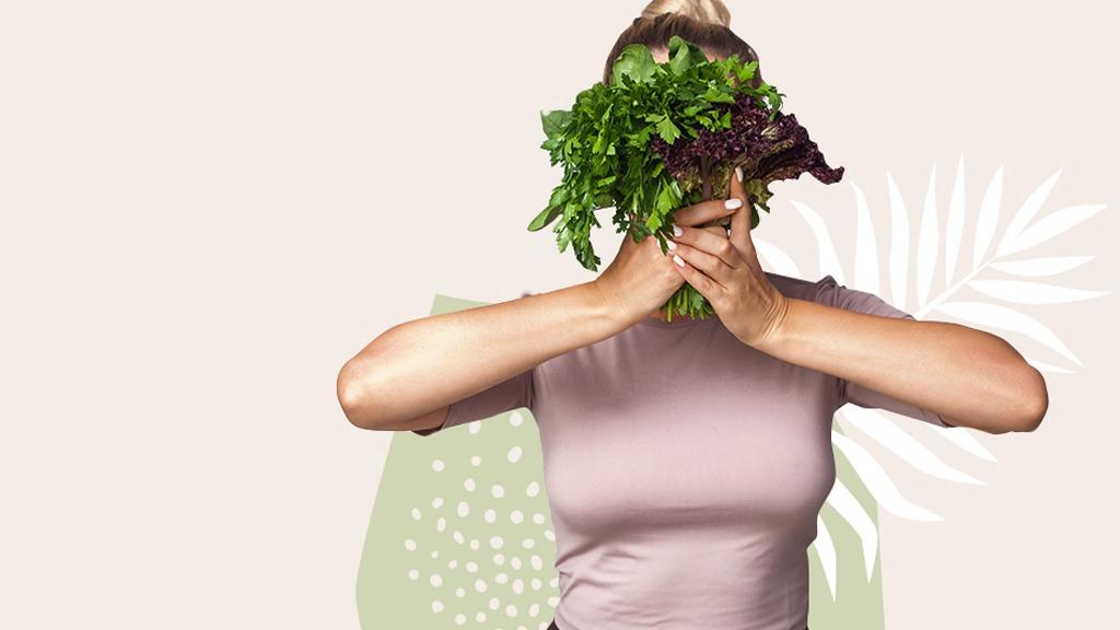Frau mit Salat in der Hand, der vor ihrem Kopf platziert ist.